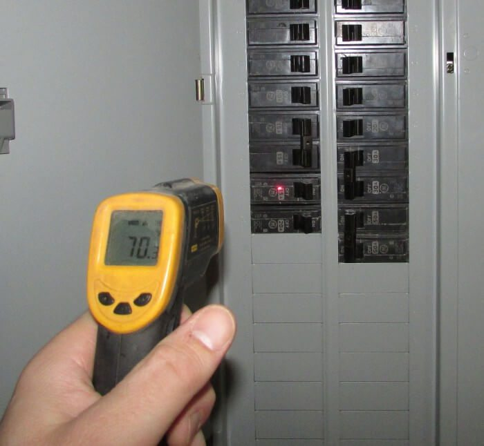 Infrared thermometer pointed at electric panel